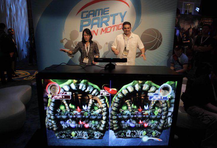 Visitantes jogam game para a câmera Kinect, do Xbox 360, em estande da Warner