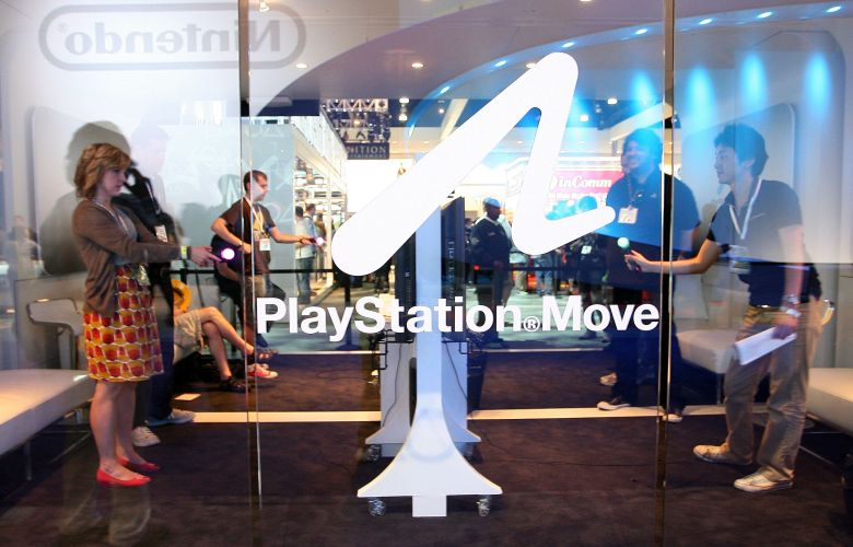 Visitantes testam o controle de movimentos PS Move no estande da Sony