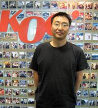 Won Lee, proprietário da KOG, em frente a um painel com fotos dos funcionários da empresa